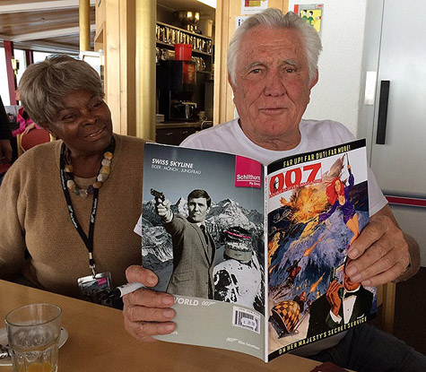 George Lazenby poses with a copy of 007 MAGAZINE while Sylvana Henriques looks on.