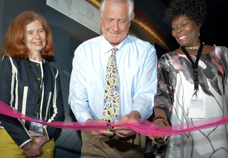 Ambassador Sarah Gillett, George Lazenby and Sylvana Henriqes cut the ribbon to open Bond World 007