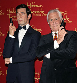 George Lazenby poses with his wax figure during Madame Tussauds Hollywood reveal of all six James Bonds as the temporary exhibit opens in the US.